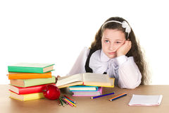 Tired little girl. In black and white school form sitting  at the table, looking in book, near - many books and red apple, isolated on white Royalty Free Stock Photo