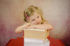 Tired little girl with books Stock Photos