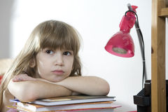 Tired little girl doing homework Stock Photo