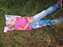 Girl dreaming on the grass. Tired little girl dreaming on the grass in summer day Royalty Free Stock Photo
