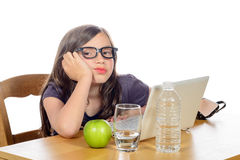 A tired little girl with her computer and an apple Royalty Free Stock Images