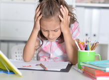 Girl holding hands on head. Tired little girl holding hands on head and looking at her drawings stock photography
