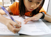 Tired little girl kid doing homework Stock Images