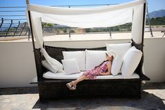Tired little girl relaxing on terrace divan Royalty Free Stock Photo
