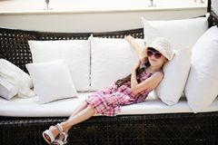 Tired little girl relaxing on terrace divan Royalty Free Stock Photography
