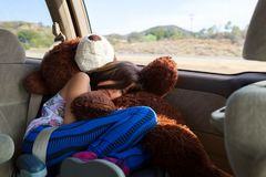 Tired Little Girl Rides Across Southwest Desert in a Booster Sea. A tired little girl rides, curled up in her booster seat atop of her big, stuffed bear, in a stock image