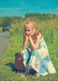 Tired little girl on rural road. Royalty Free Stock Image