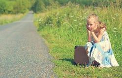 Tired little girl on rural road. Stock Photo