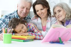 Tired little girl sleeping after doing homework while mother and Royalty Free Stock Photos