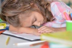 Girl sleeping on drawings. Tired little girl sleeping on her drawings royalty free stock photography