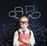 Tired little girl student on blackboard background. With science hand drawings pattern and speech bubble royalty free stock photography