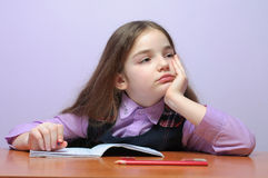 Tired little school girl doing homeworks at desk Royalty Free Stock Photos