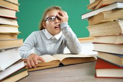 Tired little schoolgirl around books. Photo of girl in classroom. Education concept stock image