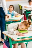 tired little schoolgirl sleeping on desk royalty free stock photography