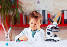 Tired little scientist writing notes after experiments in school lab Stock Photo