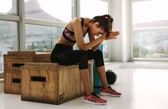 Woman relaxing after her intense workout. Tired looking fitness woman sitting on box at gym. Female relaxing after her intense workout at fitness studio Royalty Free Stock Images