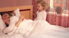 Tired loving mother woman cant sleep because of her hyperactive daughter child stock video
