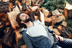 Tired lumberjack sleeping on pile of wood. Exhausted woodcutter having rest after hard work. Masculinity, manhood, handiwork, strength concept Stock Image