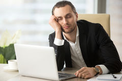 Tired male entrepreneur slumbers at work. Young man dozing with head on hand while sitting at desk with laptop in office. Businessman sleeping at workplace in Royalty Free Stock Image