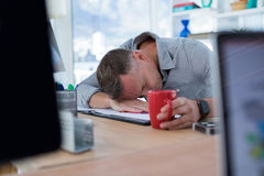 Tired male executive sleeping on desk Stock Images