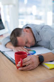 Tired male executive sleeping on desk Stock Photography