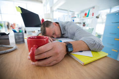 Tired male executive sleeping on desk Royalty Free Stock Images