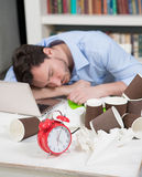 Tired male freelancer in coworking space. Close-up of alarm-clock on table while handsome male freelancer or student sleeping on his laptop computer on Royalty Free Stock Image