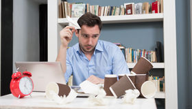 Tired male freelancer in library. Tired male freelancer looking at carton cups of tea or coffee in library. Hnadsome man looking exhausted after hard-working Royalty Free Stock Photos