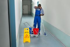 Tired Male Janitor. With Cleaning Equipment And Wet Floor Sign Stock Photography
