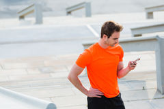 Tired male jogger dressed in orange active shirt with copy space for your brand chatting on his mobile phone Royalty Free Stock Photos
