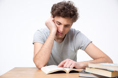 Tired male student sitting at the table. With books Royalty Free Stock Images
