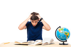 Tired male student sitting at the table and reading books Stock Photos