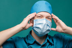 Tired male surgeon in mask on blue background, close up Stock Photography