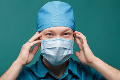 Tired male surgeon in mask on blue background, close up Stock Photos