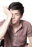 Tired male teen rubbing his eyes. Tired or lazy teenager male rubbing his eyes as waking from sleep, isolated on a white background Stock Photo