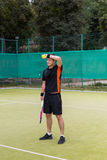 Tired male tennis player after match. Tired male tennis player wearing a sportswear holding tennis ball and  racket after the match on a court outdoor in summer Royalty Free Stock Photo