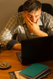 Tired male working on computer. Image of tired busy male working on computer Stock Photo