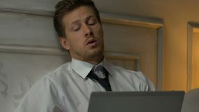 Tired male working on laptop at night, sitting in hotel room, business trip stock footage