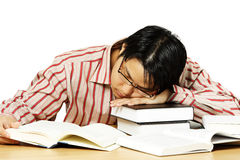 Tired man. An isolated shot of a young man falling asleep while reading books Royalty Free Stock Images