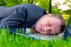 Tired man asleep on a laptop Royalty Free Stock Images