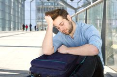 Tired man with bag sleeping at airport Royalty Free Stock Photo
