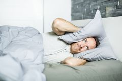 Tired man in the bed. Not happy with pillow Royalty Free Stock Images