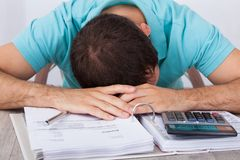 Tired man with bills and calculator at desk Stock Photo