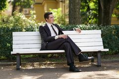 A tired man in a business suit left the office and went in the Park. he is sitting on a white bench alone and wait someone. He is alone stock image