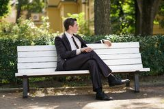 A tired man in a business suit left the office and went in the Park. he is sitting on a white bench alone and wait someone. He is alone royalty free stock photos