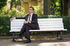 A tired man in a business suit left the office and went in the Park. he is sitting on a white bench alone and wait someone. He is alone royalty free stock photography