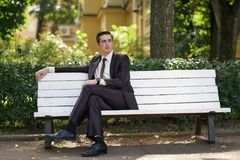 A tired man in a business suit left the office and went in the Park. he is sitting on a white bench alone and wait someone. He is alone stock images