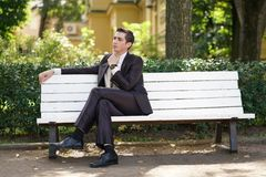 A tired man in a business suit left the office and went in the Park. he is sitting on a white bench alone and wait someone. He is alone stock photography