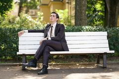 A tired man in a business suit left the office and went in the Park. he is sitting on a white bench alone and wait someone. He is alone royalty free stock images