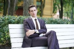 A tired man in a business suit left the office and went in the Park. he is sitting on a white bench alone and wait someone. He is alone stock photos
